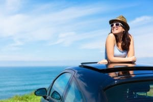 Relaxed happy woman on summer travel vacation to the coast leaning out car sunroof with the sea on background.